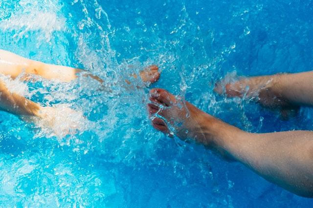 dva páry nohou šplouchající se v bazénu s průzračnou vodou