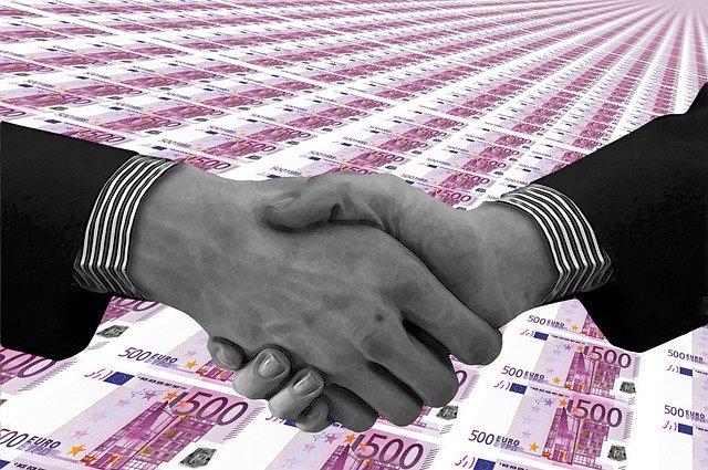 podané ruce, v pozadí euro bankovky